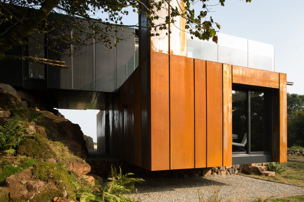 Corten Steel Cladding on this Metal Home add dimension and texture to the facade.