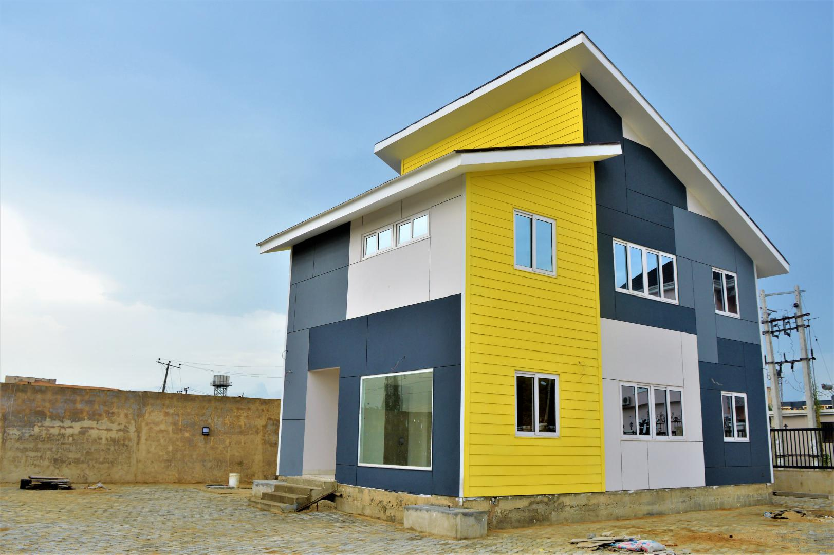 A model home in Lagos, Nigeria by Kalsi Construction using light gauge steel, features a bold yellow accent in it shiplap cladding facade.