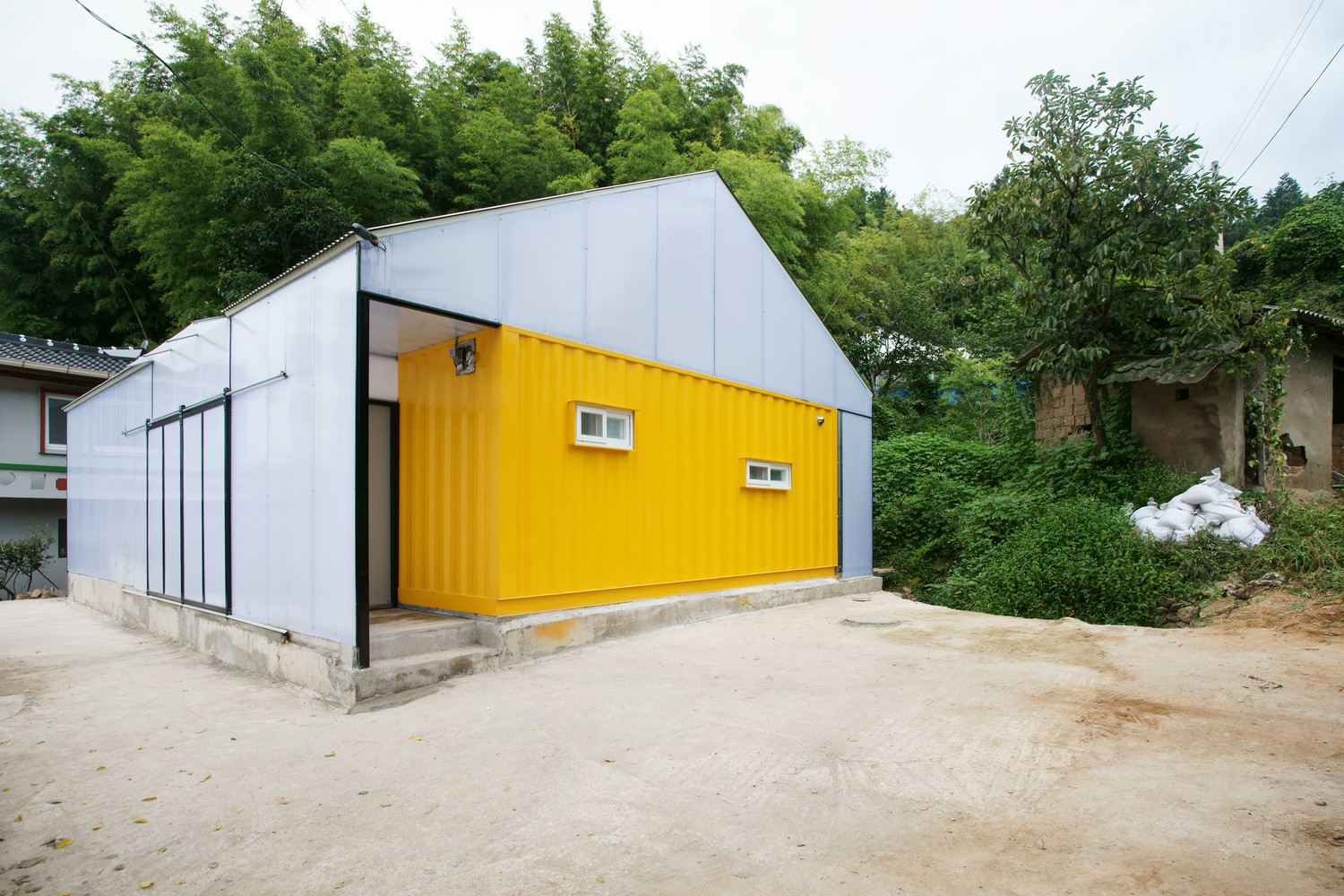A Low Cost Container House in South Korea by JYA-RCHICTECTS which features a simple gable roof