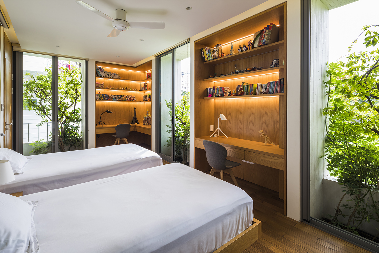 A Bedroom in Stepping Park House in Vietnam, features LED String Lights within the built-in, vertical storage/study areas.