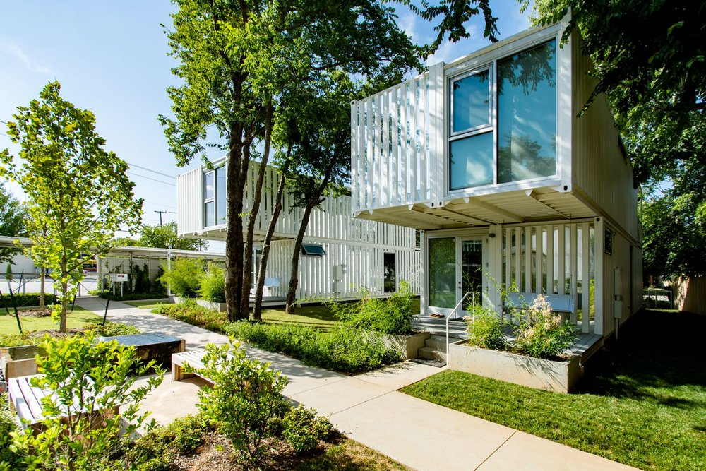 These container homes are surrounded by a lush garden with large trees.