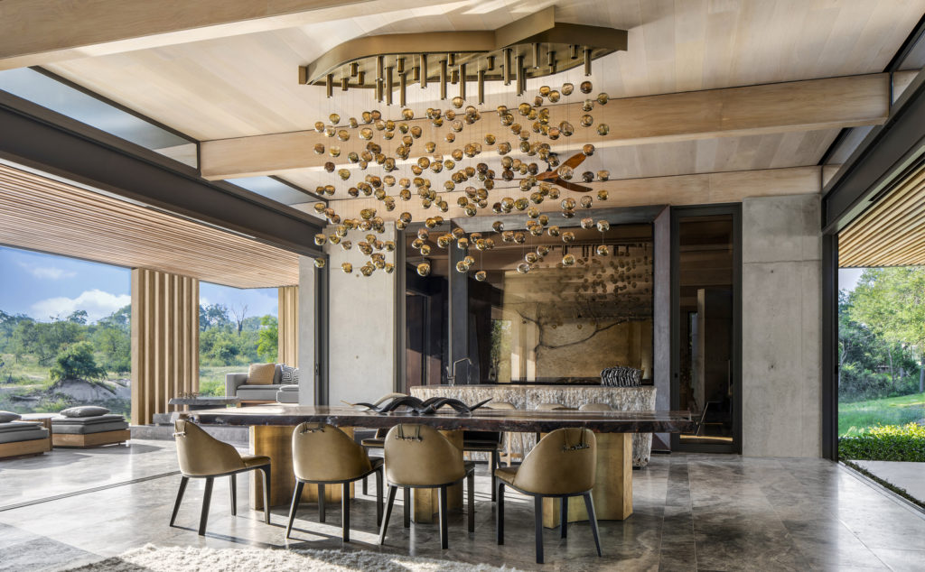 The Cheetah Plains Game Lodge in South Africa features a prominent dining area with a dramatic hand-blown cascading glass chandelier as the focal point.